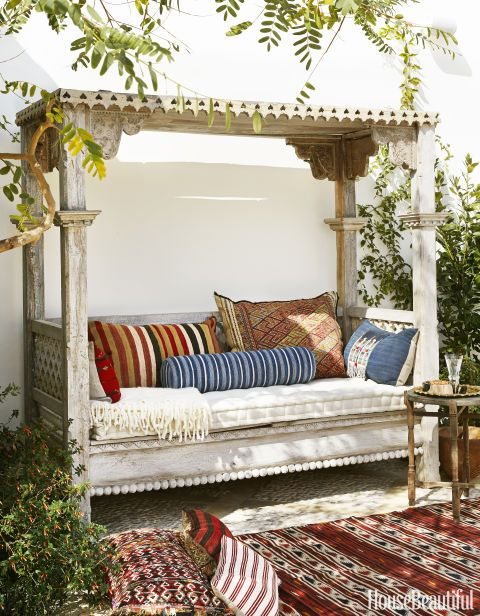 Vintage textiles enliven an Indonesian daybed outside a Richmond, Virginia, home. Click through for more patio and outdoor room design ideas.