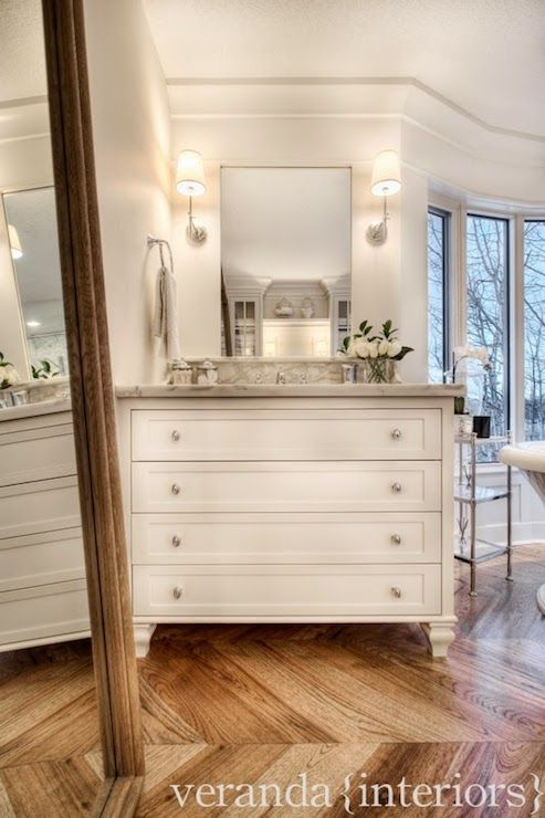 Gorgeous bathroom with leaning Restoration Hardware Levico Mirror in Natural atop large scale, herringbone hardwood floors in front of a white dresser style vanity with feet accented with nickel pulls and a gray marble countertop