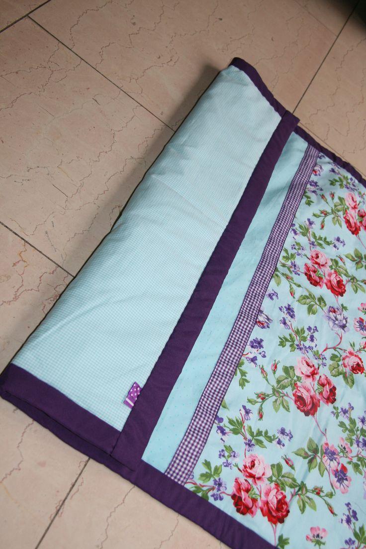 Wiegendeken in lichtblauwe stip / bloemen. Onderkant is kleine lichtblauwe ruit. Omzoomd met donkerpaarse band. 0.70 x 0.90m. Nu te koop voor €24,95