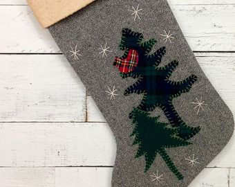 RUSTIC WOODLAND BEAR CHRISTMAS STOCKING ~This stocking is made from a pale brown/blue plaid wool fabric. The backing fabric is the same as the front. ~The bear is made from brown tweed wool fabric. ~The pine trees are made from dark green wool and plaid green wool fabric. ~The snow flurries are made from vintage white buttons. ~The bear and trees are all hand cut and hand sewn onto the stocking using embroidery floss. ~The stocking is lined with muslin fabric. ~The cuff is hand tea-dyed…