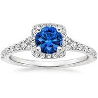 This glamorous halo setting features a row of vibrant blue sapphires set around the exterior edge of the halo. Additional diamonds on the gallery and on the split-shank band create an effect of magical shimmer.