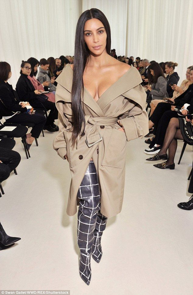Gravity-deying: Braless Kim Kardashian showed off her ample cleavage in off-the-shoulder trench coat and thigh-high boots at the Balenciaga PFW show on Sunday