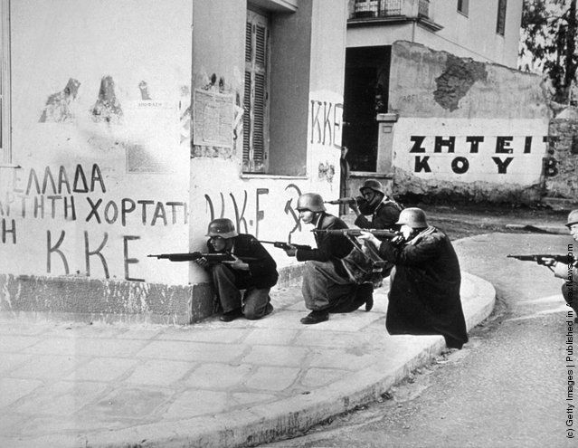 Steel-helmeted Elas troops use a corner building as a shelter as they fire at police headquarters during a civil uprising in Athens. (Photo by Keystone/Getty Images). Circa 1944