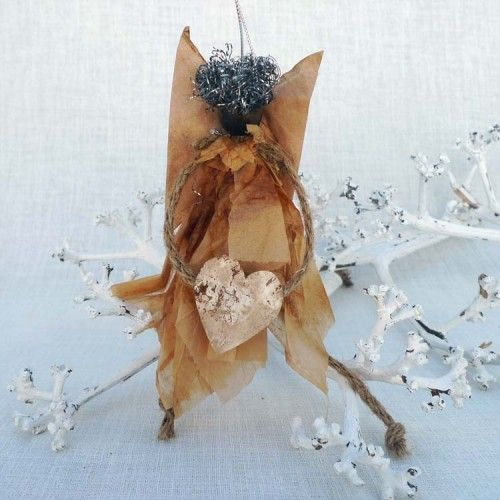 Angel holding a heart with wings and skirt made of recycled tea bags.