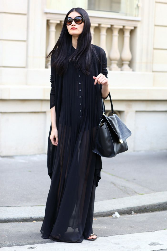 Ming Xi at Paris Couture in a sheer black pleated maxi dress, long knit cardigan, and black #Celine bag | Photo by Phil Oh / Street Peeper