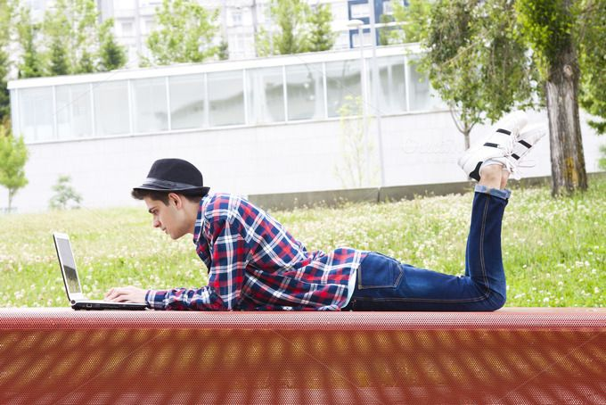 young man with laptop outdoors by pruden.alvarez on @creativemarket