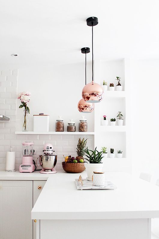 Bright white kitchen with metro tiles, plants and copper lamp shades