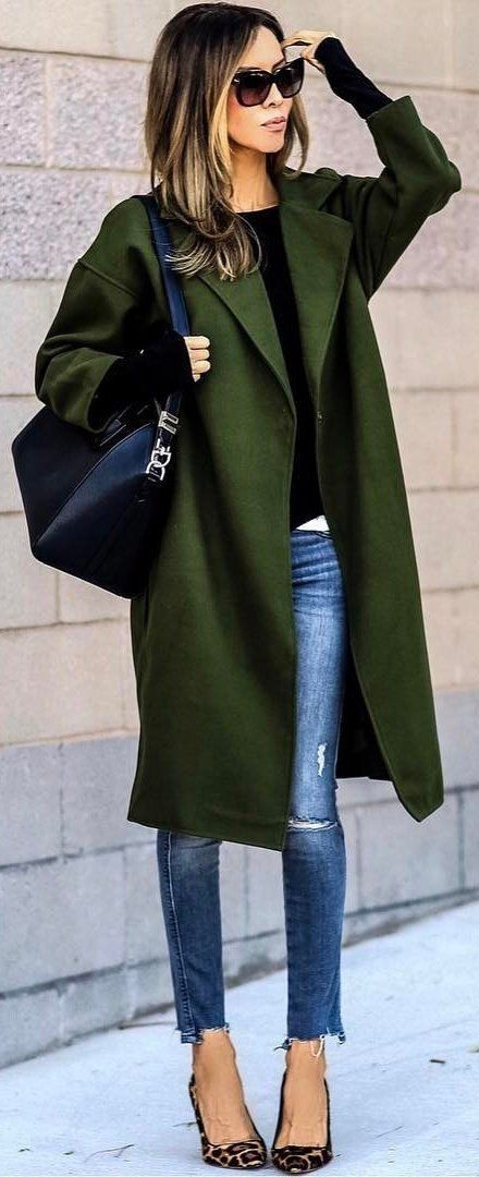 Hunter green coat over black sweater and blue jeans.