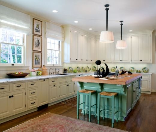 traditional white cabinets with white wall accents are warmed up by the butcher block island countertop - Eclectic Kitchen Cabinets