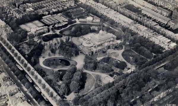 Luchtfoto van de Haagsche Dierentuin in 1928. Midden voor is de hoofdingang met direct daarachter de papegaaienlaan die rechtstreeks naar het Hoofdgebouw leidde. Direct voorbij de bomenrij van de papegaaienlaan zie je links en rechts twee grote vijvers waarin diverse watervogels vertoefden. De vijver rechts was met een net overspannen. Helemaal bovenin de hoek werd later de Bokkenrots gebouwd en rechts van de kassen kwam later een apenhuis en de uilenruine.