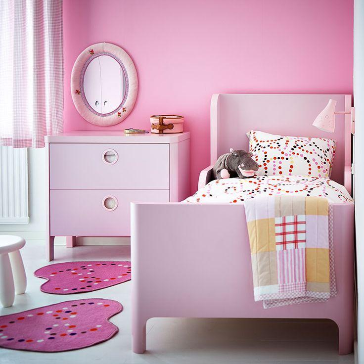 Una cama extensible rosa claro con una cómoda a juego