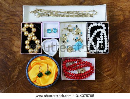 necklaces, rings, earrings, pearls and gold in boxes on a wooden background