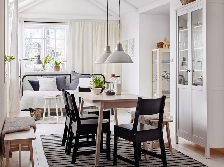A medium-sized dining room furnished with a white stained solid birch table and four black chairs combined with a white stained solid birch bench.