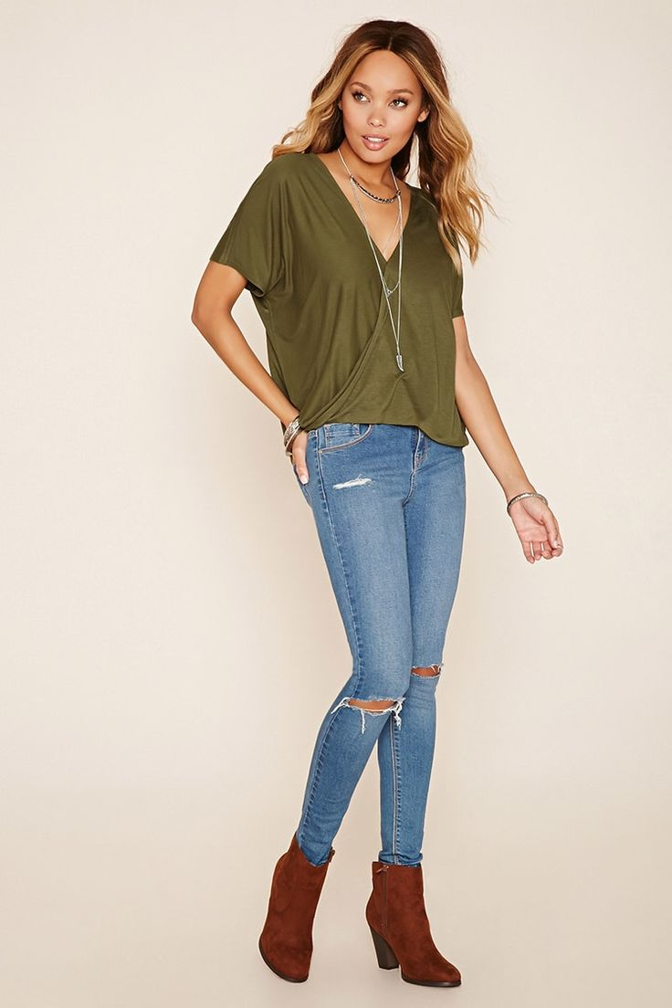 A knit top featuring a surplice neckline, a twisted front hem, and short dolman sleeves.