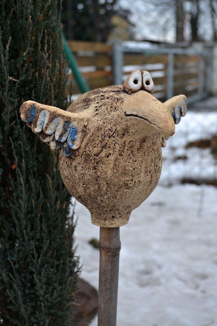 Pták na tyči Pták je ručně modelován z hrubé šamotové hlíny, pálený na vysokou teplotu. Barven oxidem, dobarvován bílou glazurou a modrou engobou. Pták je určen k usazení na tyč do záhonu. Velikost cca 25x 18 cm