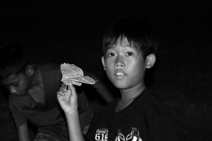 Boy with paper plane at a night market, Phnom Penh
