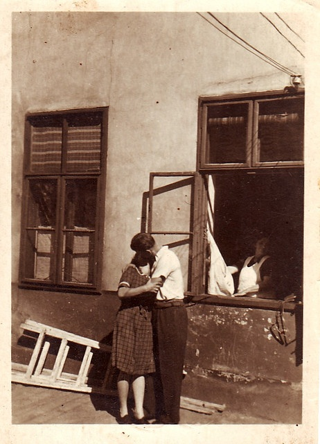 A couple steals a passionate kiss as another woman looks on from a nearby window in this endearing, undated image that might to be from the late twenties or early thirties.
