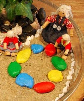 stgl de grote wereld poppetjes en kring gekleurde stenen