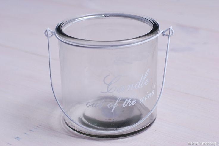 Minimalistyczny lampion w kształcie słoja z grubszego szkła. Metalowy uchwyt pozwoli na zawieszenie ozdoby. Może posłużyć jako wazon lub oświetlenie domowej werandy.