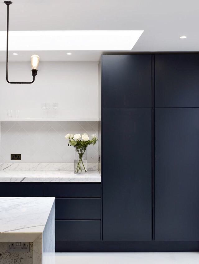 Smooth Panel Navy Cabinets With White Counters And White Wall