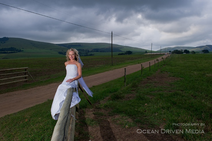 Bride on fence with dramatic sky in the background