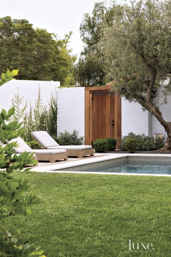 For the entrance courtyard of a Beverly Hills house reinvented by designer Ryan White, landscape designer Christine London lined a path of gray limestone pavers with lavender and old-growth manzanilla olive trees. A stucco wall encloses the property and offsets a teak gate accented with bronze hardware.