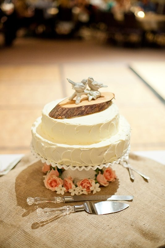 Wedding cheesecake with rough frosting, on a vintage milk glass Fenton cake stand. Homemade wood slice cake topper.