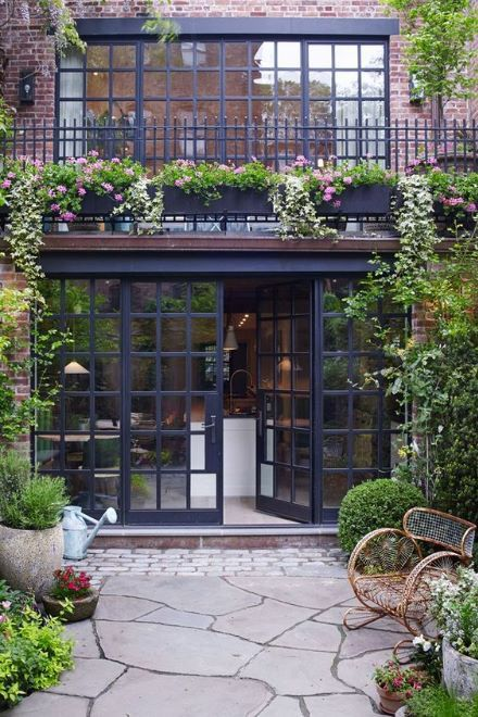Perfection. Steel Windows, iron railings, stone patio and plants all around.