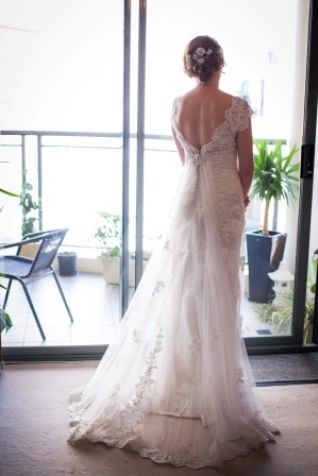 Stunning. With sophisticated vintage appeal, this embellished lace gown features a scalloped V-neckline and plunging low back with delicate illusion short sleeves. The back of the gown features a beaded brooch detail with a soft tulle train fastened into the zipper and self covered button closure.