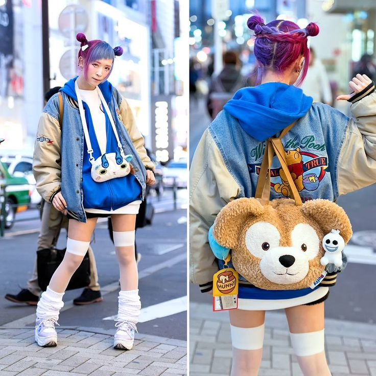 Reo on the street in Harajuku with a colorful double buns hairstyle, a resale Winnie The Pooh bomber jacket, a Duffy backpack, Yokai Watch pouch (with retro video game inside), plush Dragon Quest slime. WC platform shoes, and loose socks. Reo is a Monster Girl at Kawaii Monster Cafe Harajuku!