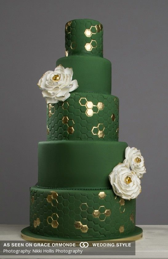 Deep green fondant with alternate smooth and honeycomb pattern tiers accented with white sugar flowers and gold metallic