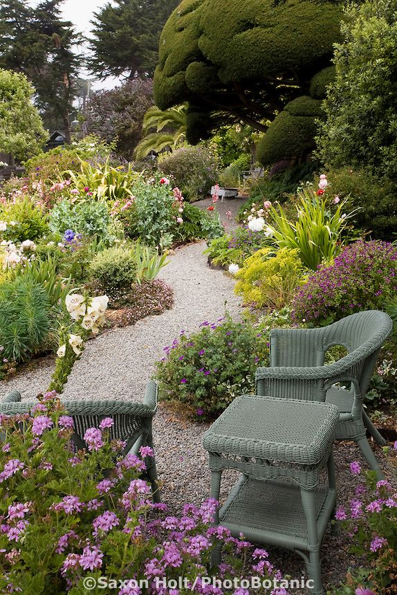 Sitting area by winding gravel pathway in colorful cottage garden.