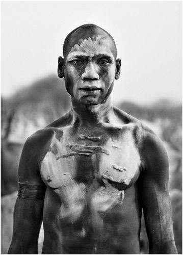 Africa | This Dinka man, photographed at the cattle camp of Kei in southern Sudan, 2006, covers himself in ash from a burnt cow patty. The ash helps keep harmful insects away. | ©  Sebastião Salgado