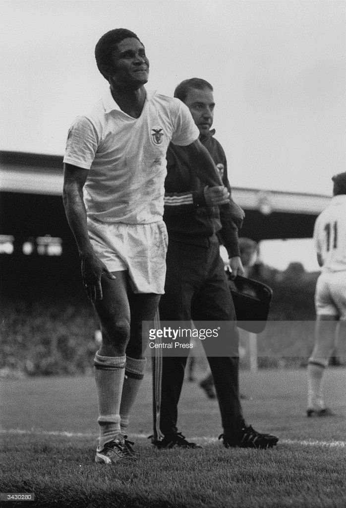 A trainer helping the Benfica and Portugal footballer, Eusebio, leave the pitch.