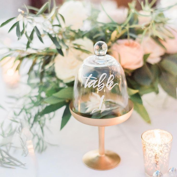 Say hello to your new favorite garden wedding table number idea. These unique cloche table numbers don't just incorporate a floral print, they include the real thing in their three-dimensional displays. #marthaweddings