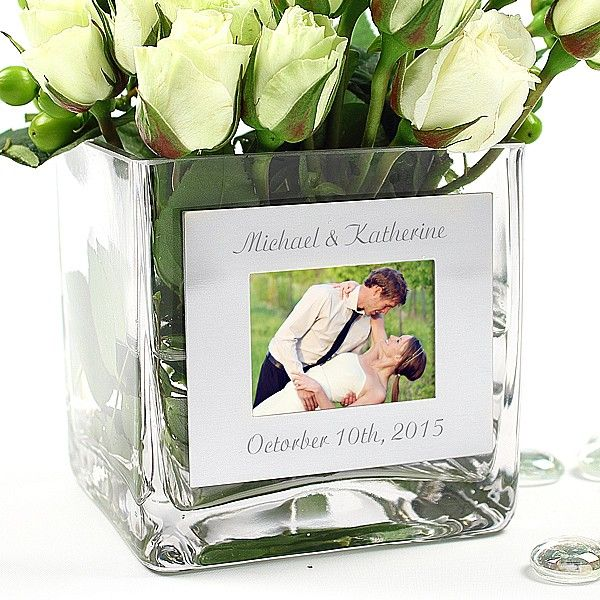 Decorate wedding reception or party tables with these Square Glass Vases with Engraved Photo Frames. The clear glass vases are square shaped and feature a metal photo frame on one side. The frame can be personalized with up to two lines of custom text at no additional cost. These personalized pieces become keepsakes after the wedding day or party.