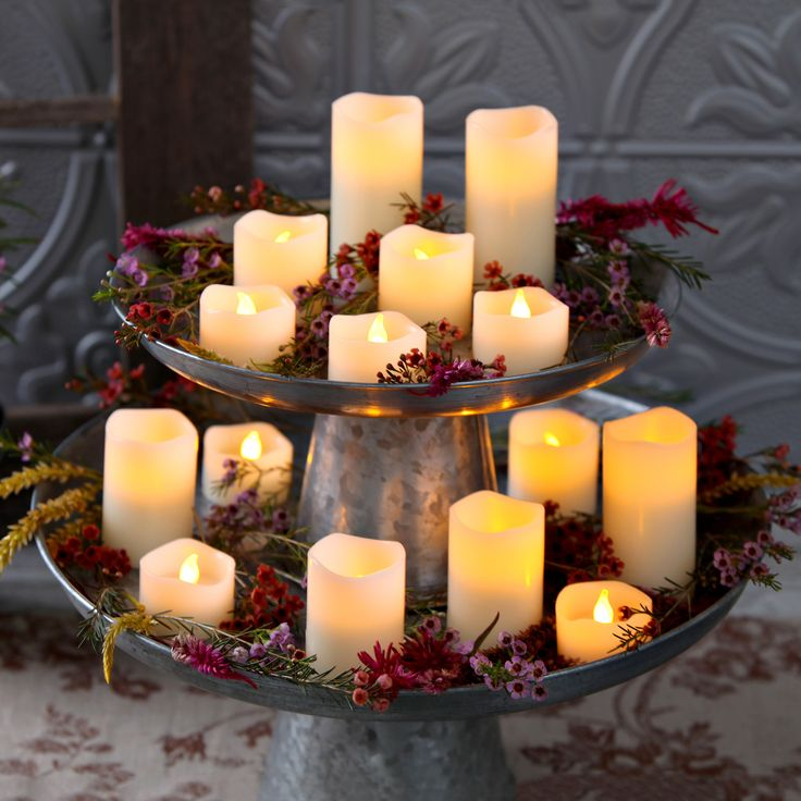 Set a romantic scene with a set of flameless candles, fresh flowers and simple rustic tin cake stands, stacked for height. This makes a great table centerpiece or entryway decor for a wedding, anniversary, dinner party, or a Valentine's Day dinner for two. Keep the mood going: each battery-operated wax candle emits a warm flickering glow from a single LED and includes an automatic 6-hour timer! From Lights.com