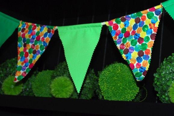 Eric Carle fabric at a local quilting store and paired it with solid green fabrics to make many yards of bunting