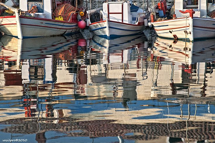 Fishing boats and reflections in the small old port in Myrina; the capital of Lemnos Island.