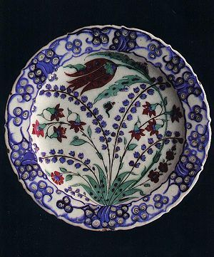 Naturalistic flowers such as hyacinths, carnations and tulips began to appear in Iznik ceramics during the reign of Suleyman the Magnificent. This 16th century plate with a design of cloud bands and spirals around the rim id decorated with a large tupip curving anticlockwise. Iznik plate. PRIVATE COLLECTION
