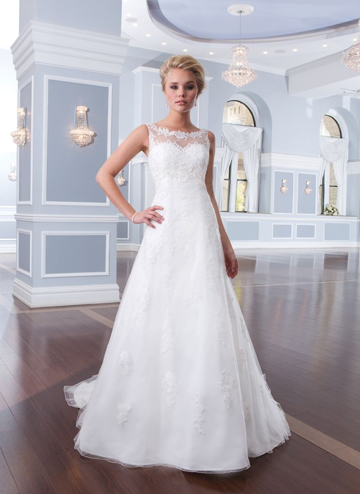 Lillian West style 6300 This tulle and beaded lace A-line gown has an illusion Sabrina neckline and chapel length train. Satin buttons enclose the illusion back neckline and zipper.