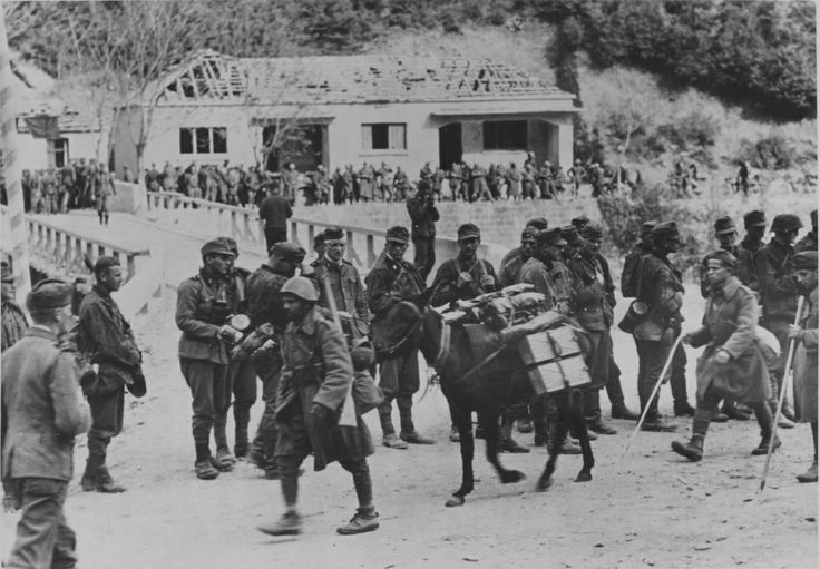 Greece, 1941: Italian marines trudge past German troops after the collapse of Greece in April. The Germans made little effort to conceal their lack of admiration for the Italian fighting spirit, with the Italian invasion of Greece in Oct 1940 pushed back and defeated despite the Italians' overwhelming superiority in numbers, weapons, and equipment.