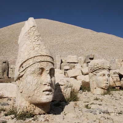 Whose heads are lying in Mount Nemrut, a major tourist attraction in Turkey? Various Greek and Iranian gods! Mount Nemrut is a 2,134 m (7,001 ft) high mountain in southeastern Turkey. Near the summit, a number of large statues of Greek and Iranian gods are erected around the royal tomb, which King Antiochus I Theos of Commagene built for himself in 62 BC. The heads of the statues have at some stage been removed from their bodies, and they are now scattered throughout the site.