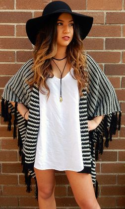 Tangier Poncho by SAN JOSE features a black and white crochet pattern with fringe detailing all around the hemline. The women's poncho comes down to approximately the mid thigh and has a relaxed flowy fit.