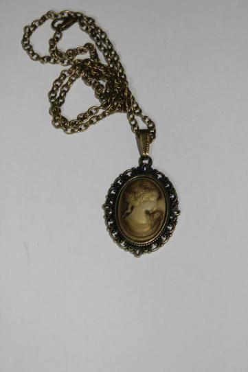 Collar bronce con un camafeo y un cabuchón de resina con el busto de una mujer en marrón. La cadena mide 50 cm aprox. pero se puede ajustar por encargo. - See more at: http://lookestilo.com/portfolios/artesania-mr/productos/collar-bronce-camafeo-resina-marron#sthash.0xCs0W6K.dpuf