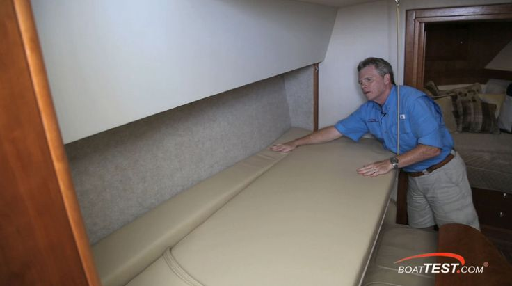 Albemarle 360 Express Fisherman: Here one can see the Pullman berth, plus the lower sofa converted to another berth. (Captain Steve's knee is on it.) The dinette table is a bit small, but the salon/galley is roomy enough to allow plenty of movement. Notice the Amtico flooring.