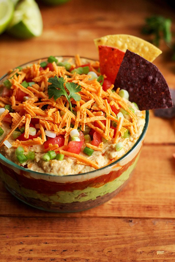 The BEST Vegan 7 Layer Dip - Homemade low-fat refried beans, creamy guacamole, zesty tomato salsa, hummus (no need for sour cream!), vegan cheese, and fresh chopped tomato & green onion! #vegan #glutenfree - ilovevegan.com