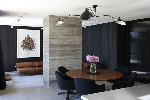 The verticality of the cedar tongue and groove is offset by the off-shuttered concrete column, which separates the dining area from the lounge and houses a fireplace.