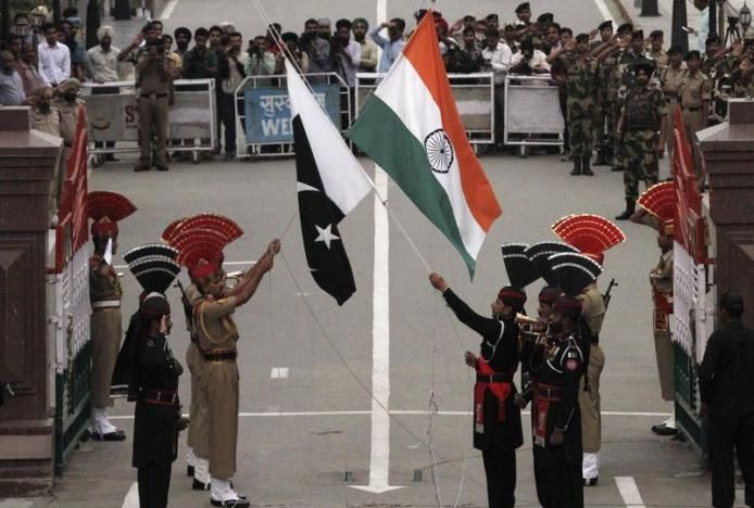 Pakistani rangers (wearing black uniforms) and Indian Border Security Force (BSF) officers lower their national flags during a daily parade at the Pakistan-India joint check-post at Wagah border, near Lahore November 3, 2014.  REUTERS/Mohsin Raza