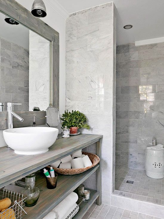 Serene Strokes~The roomy walk-in shower forgoes a cumbersome door allowing the polished white marble to take center stage. Soft gray veining in the marble provides a visual connection to the weathered look of the vanity. Although the marble was purchased as contemporary 12x12-inch tiles, they were cut in half and installed in a more vintage-flavored running-bond pattern.